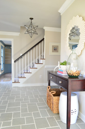foyer entryway with gray slate tile floor and clean white grout lines including pretty mirror and star pendant light