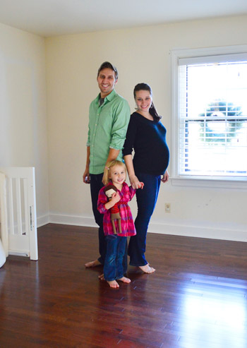 family with pregnant wife in room to turned into nursery