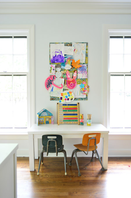 small fabric covered cork board used to pin up kid art projects above small homemade desk and schoolhouse style chairs