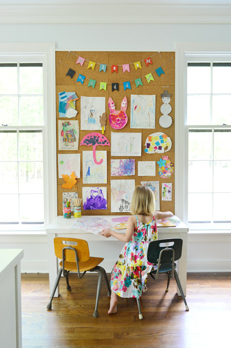 Kids Art Displayed On Large Cork Board Wall In Home Office Above Desk