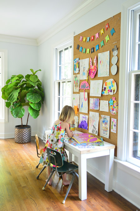 child working on art below giant cork board wall with drawings and painting pinned up