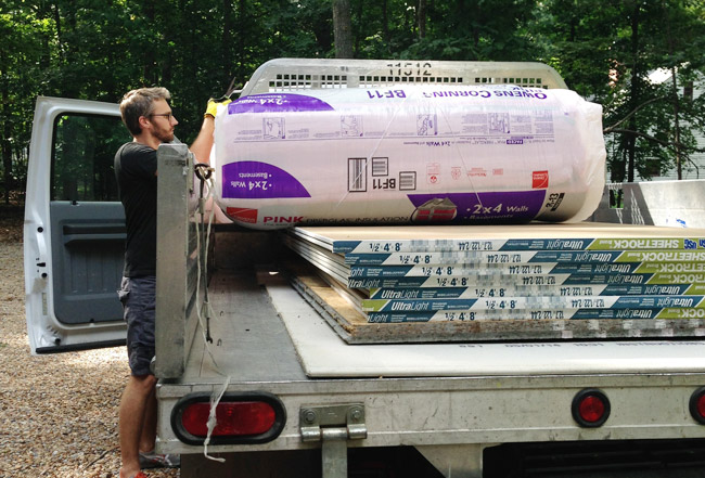 John lifting insulation out of truck bed with sheets of sheetrock in the back too