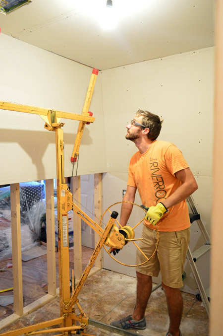 John lifting drywall panel into place on laundry room wall