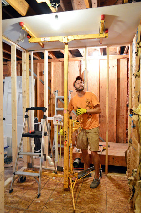 John using drywall lift to hold sheet of sheetrock to ceiling