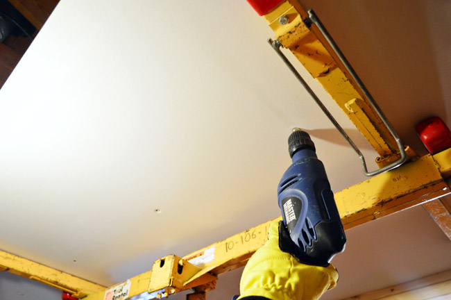attaching drywall sheet to the ceiling using a drill