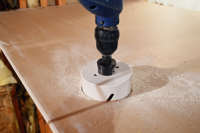 drill with hole cutting bit attached sawing through drywall sheet