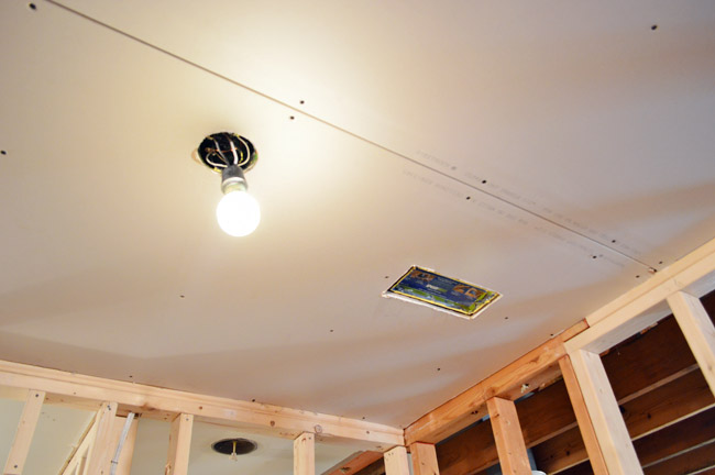 drywall hung in ceiling with hole cut for light and HVAC vent