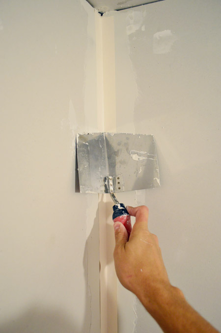 corner trowel pressing tape into corner of drywalled room