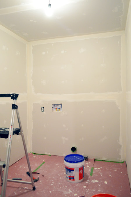 small room with one coat of drywall tape and mud applied