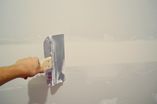 John dragging large drywall knife over seam in drywall to smooth mud