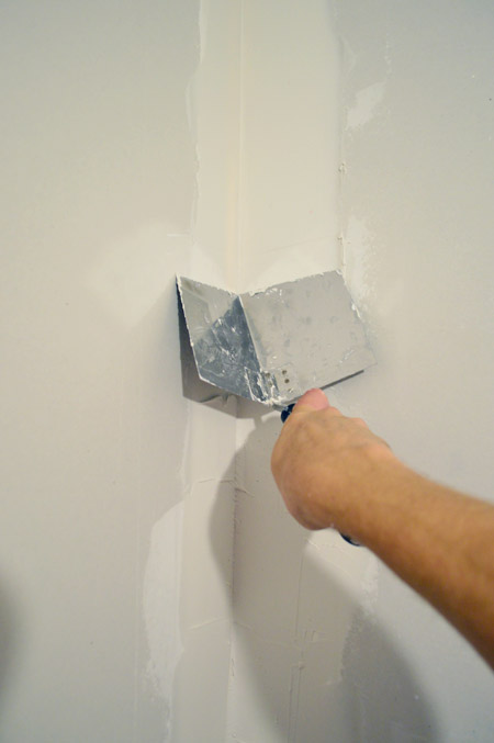 John smoothing drywall mud in corner of room using corner trowel