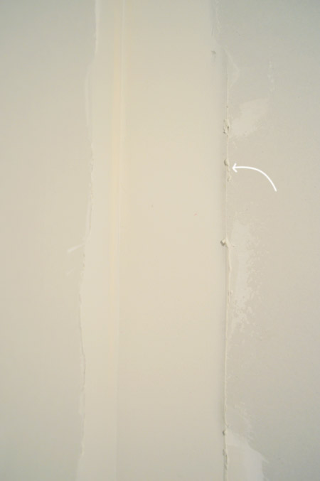 arrow pointing to ridge in drywall mud after scraping excess