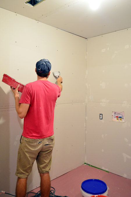 John applying mud over drywall screw head marks
