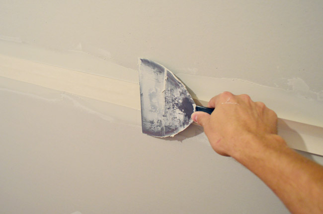drywall knife smoothing tape into drywall tape and bottom layer of mud