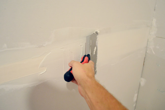 larger drywall knife being dragged across tape to apply another layer of mud