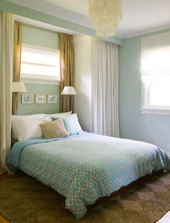 blue bedroom with curtain panels on all sides creating built in nook with wall sconces with blue bedspread and jute rug and capiz chandelier